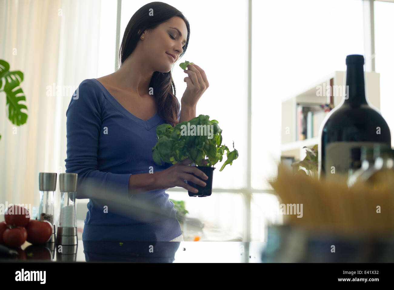 Young woman smelling basil plant in kitchen - Stock Image
