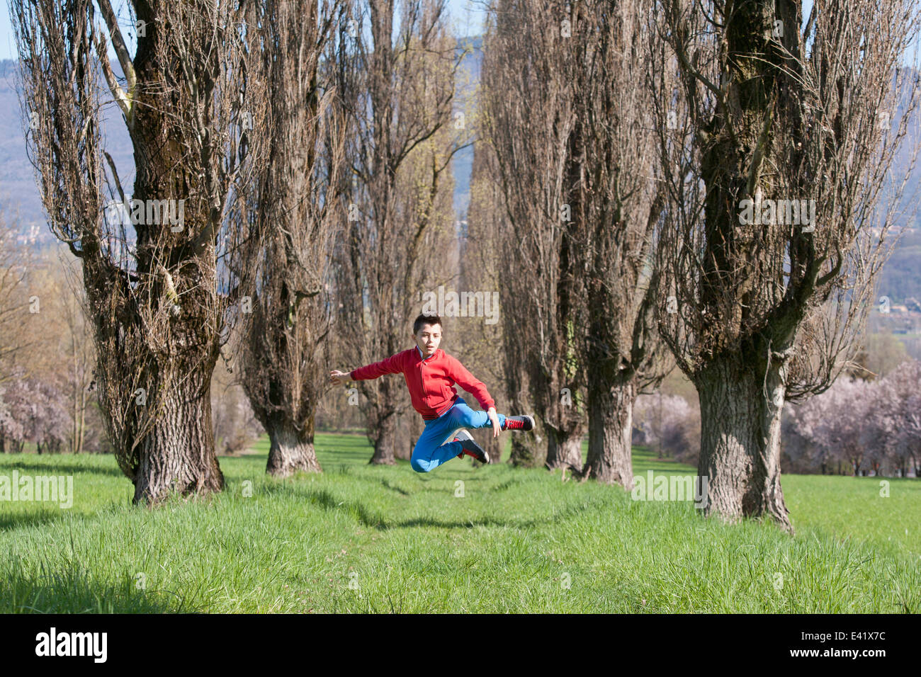 Twelve year old boy jumping mid air in tree lined field - Stock Image