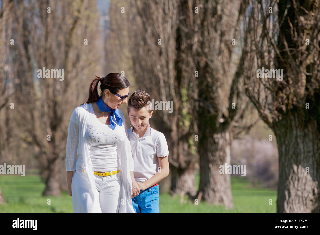 Twelve year old boy and mature mother strolling and chatting - Stock Image