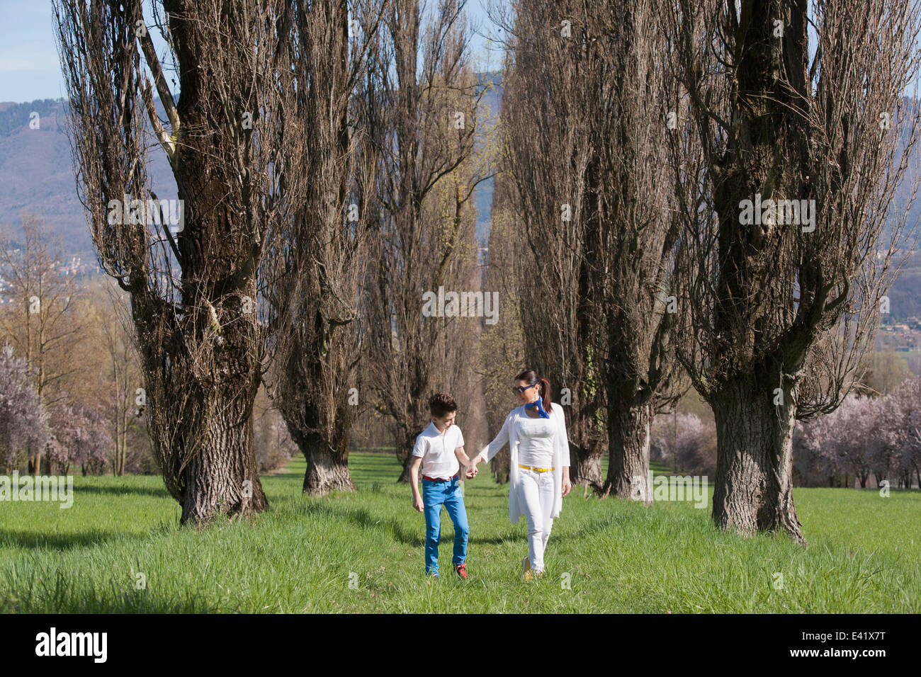 Twelve year old boy and mature mother strolling along tree lined field - Stock Image