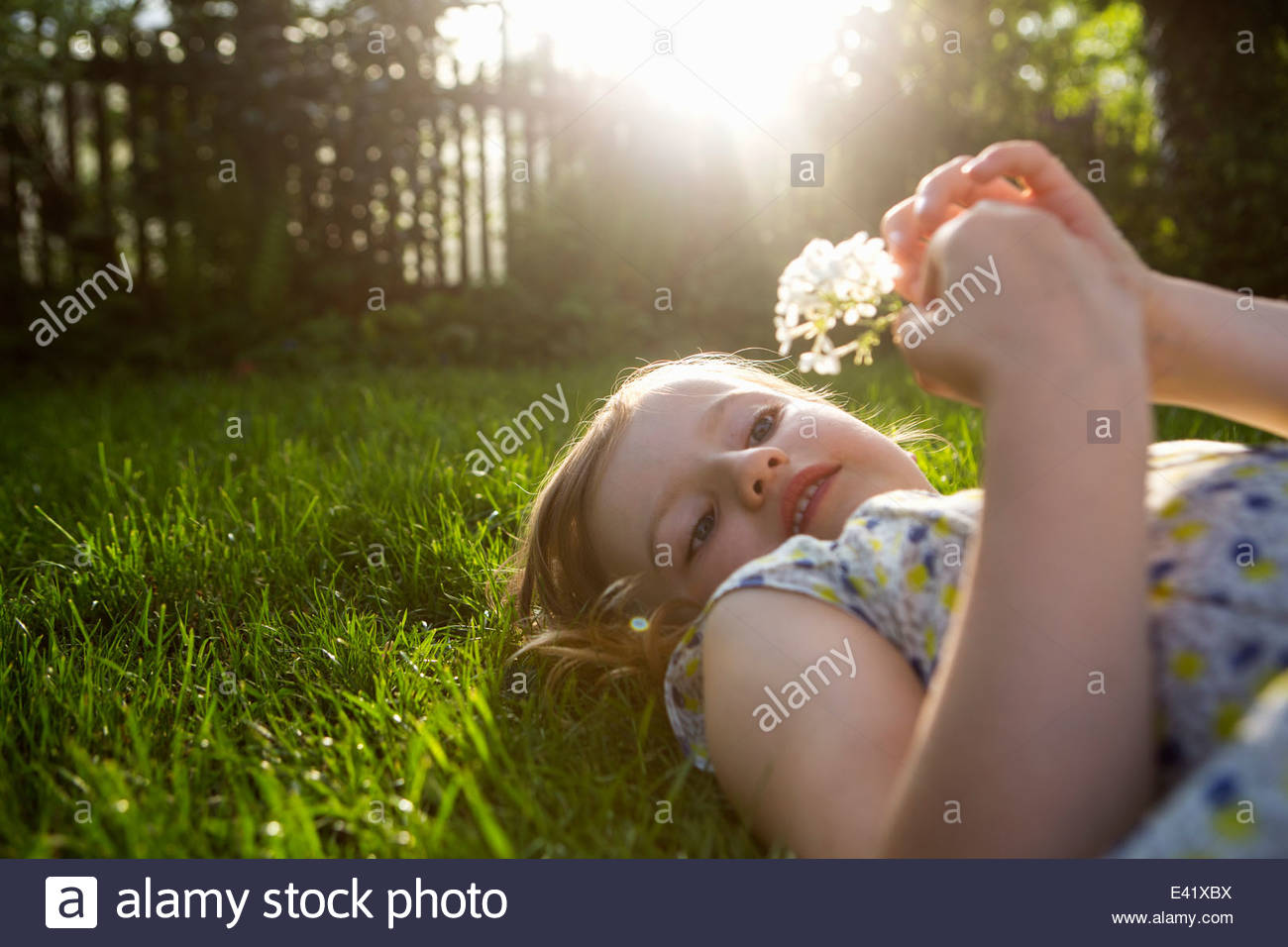 Girl with dandelion clock, lying on back on grass Stock Photo