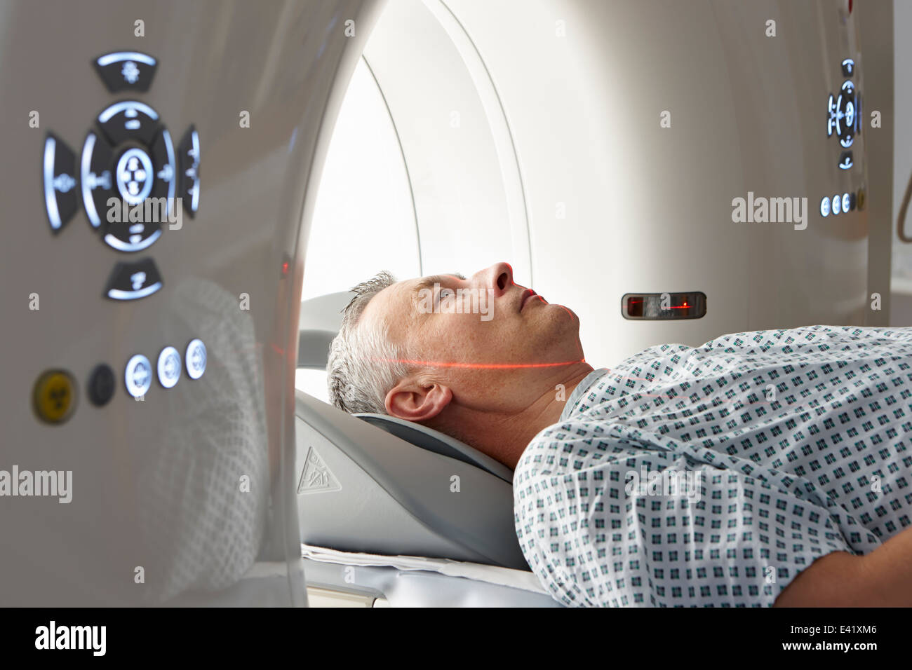 Man going into CT scanner - Stock Image
