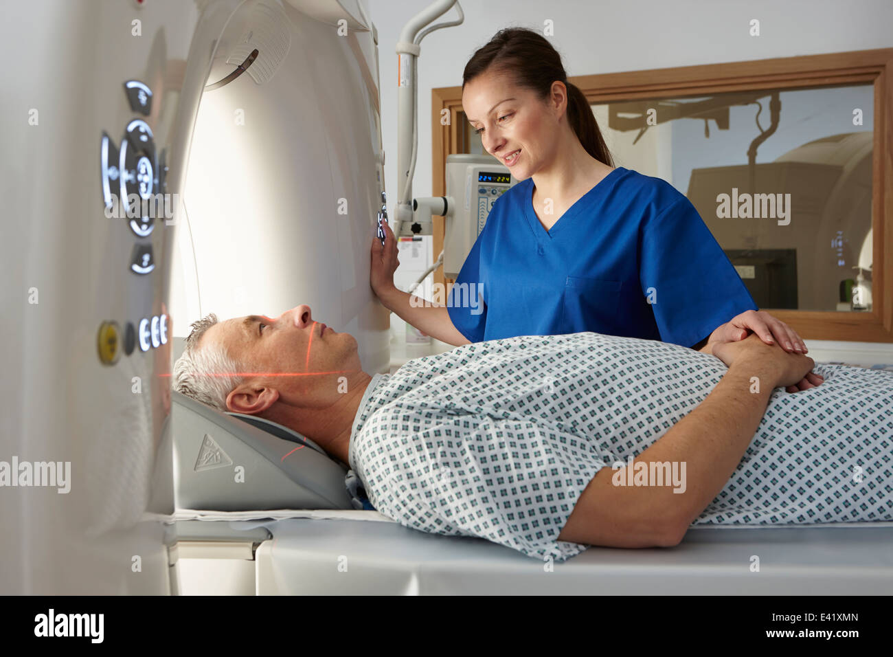 Radiographer reassuring man going into CT scanner - Stock Image