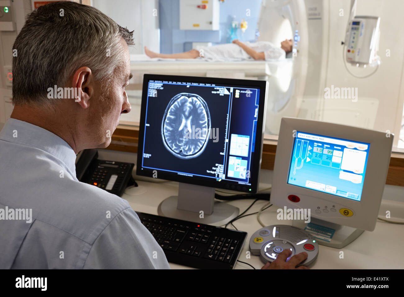 Radiologist looking at brain scan image on computer screen - Stock Image