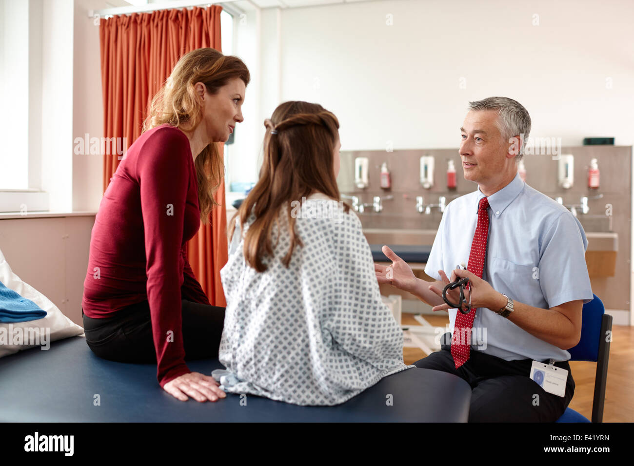 Doctor talking to patient and mother - Stock Image