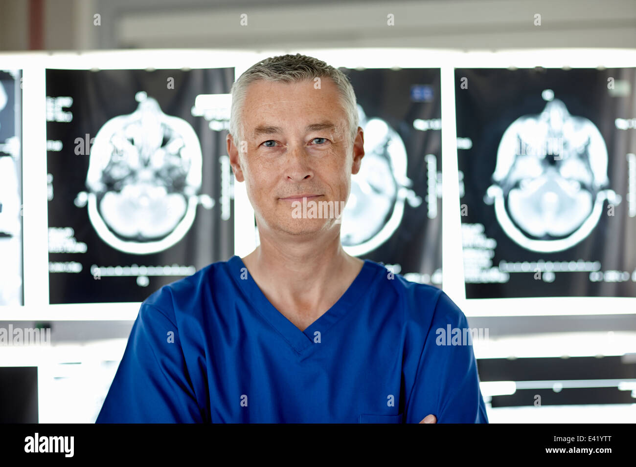 Radiologist standing in front of brain scans - Stock Image