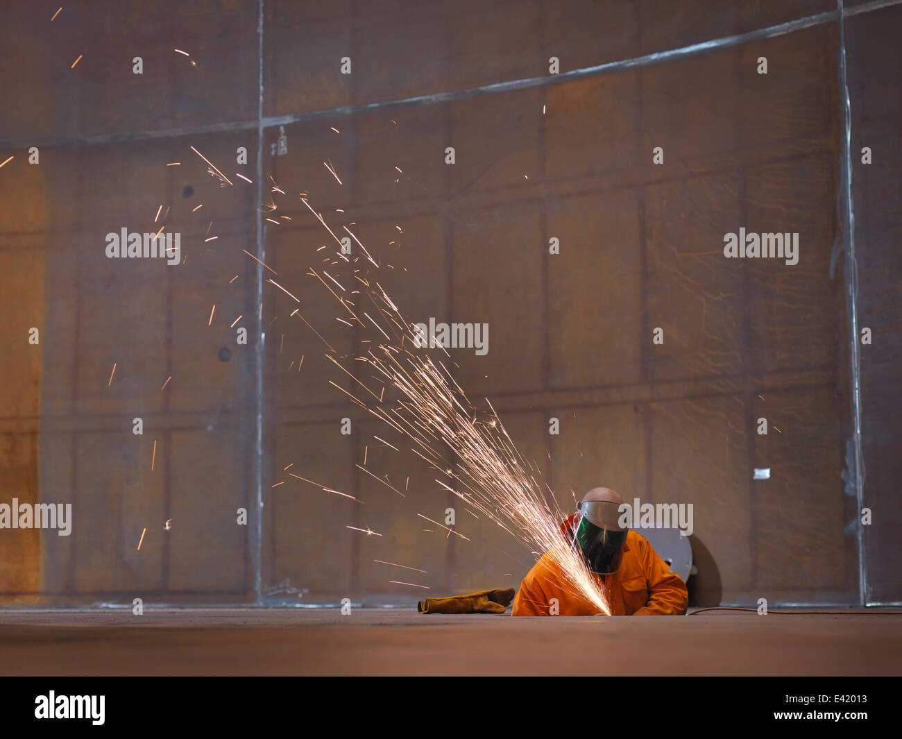 Worker grinding in marine fabrication factory - Stock Image