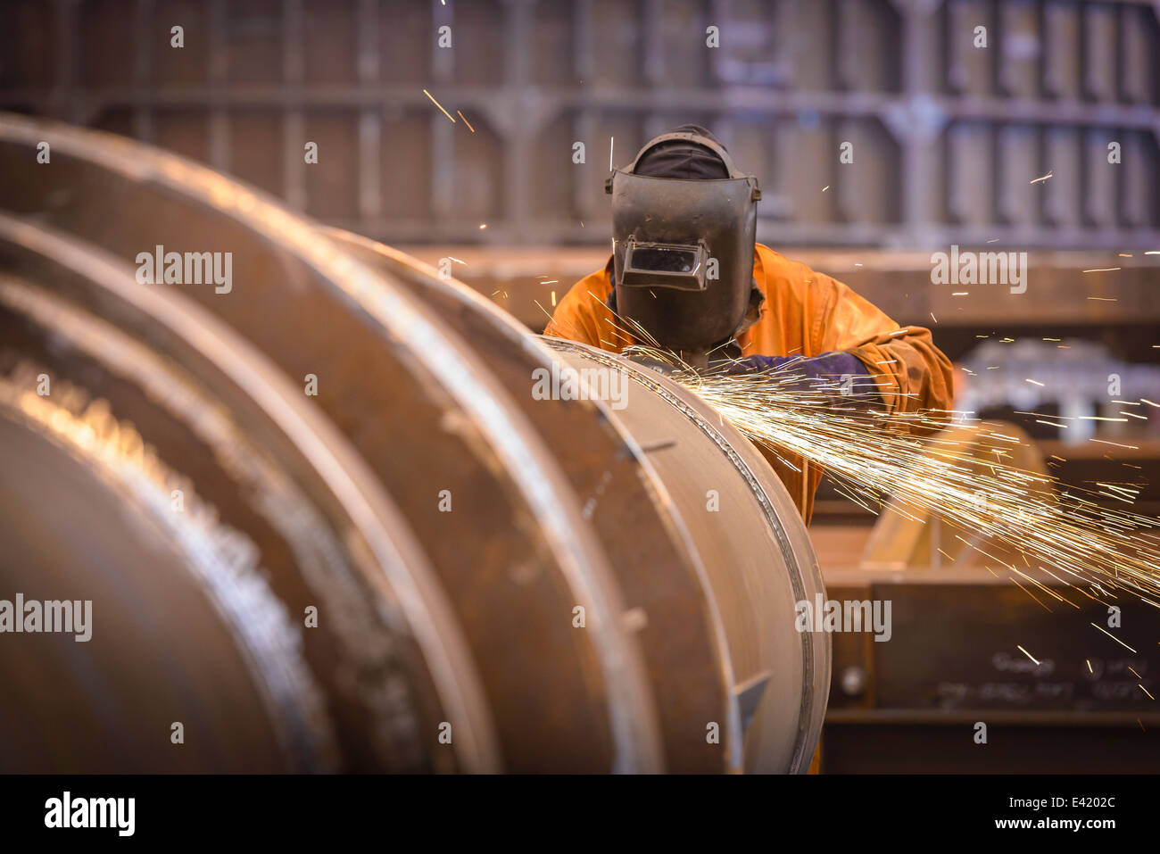Worker grinding metal construction in marine fabrication factory - Stock Image