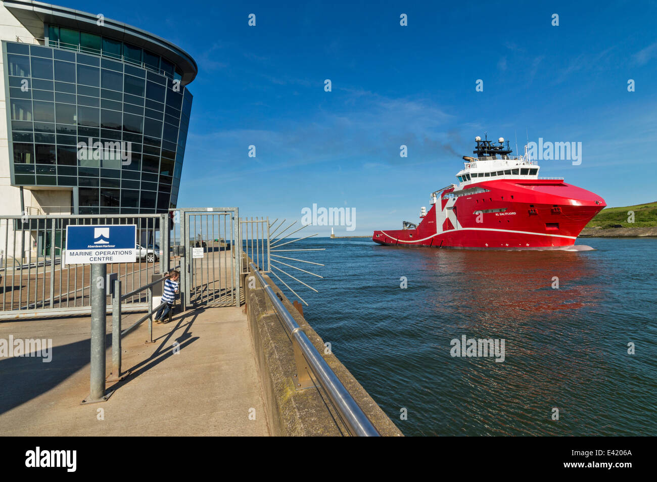 RED NORTH SEA OIL SHIP PASSING THE MARINE OPERATIONS CENTRE NORTH PIER ABERDEEN HARBOUR SCOTLAND - Stock Image
