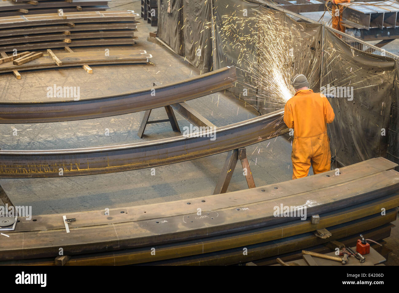 Worker grinding metal construction in marine fabrication factory, high angle view - Stock Image
