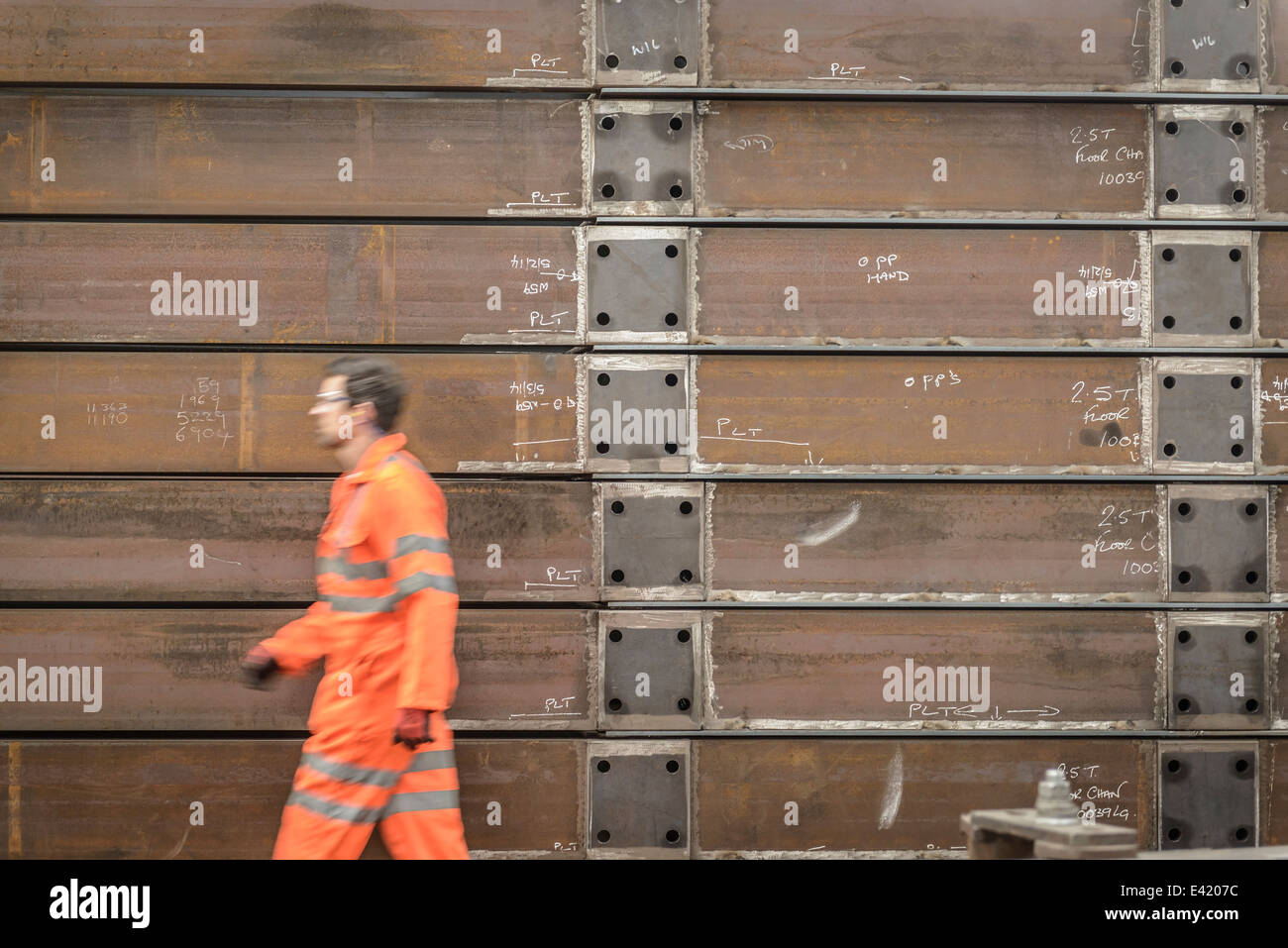 Engineer walking past marine fabrication in factory - Stock Image