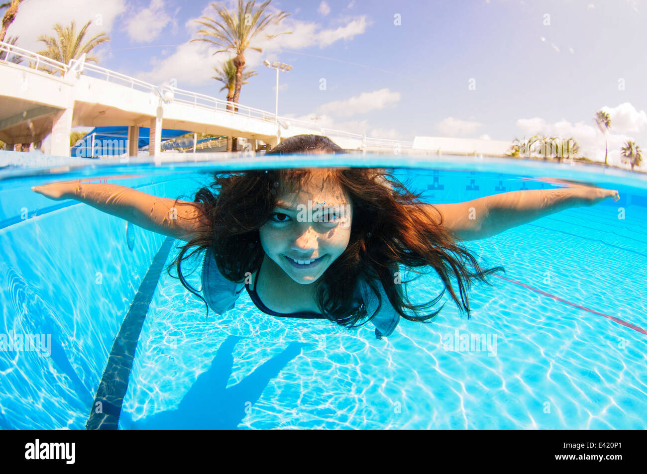 Girl free diving under water in swimming pool - Stock Image