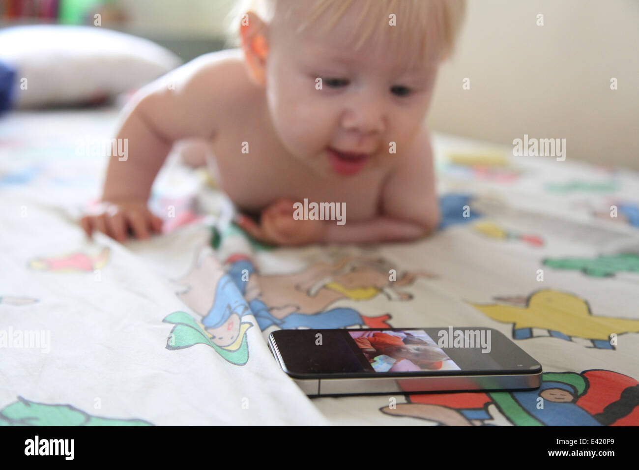 Baby plays with smartphone on bed - Stock Image