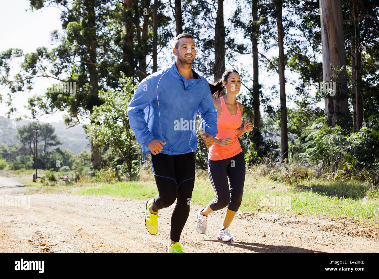 Young couple jogging in forest - Stock Image