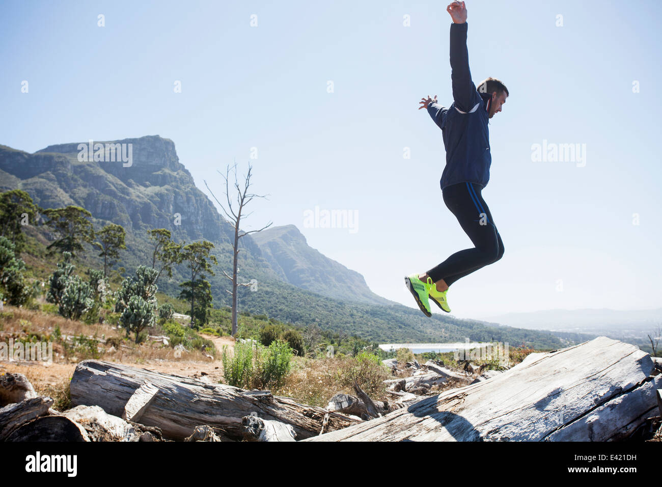 Male jogger jumping in mid air - Stock Image