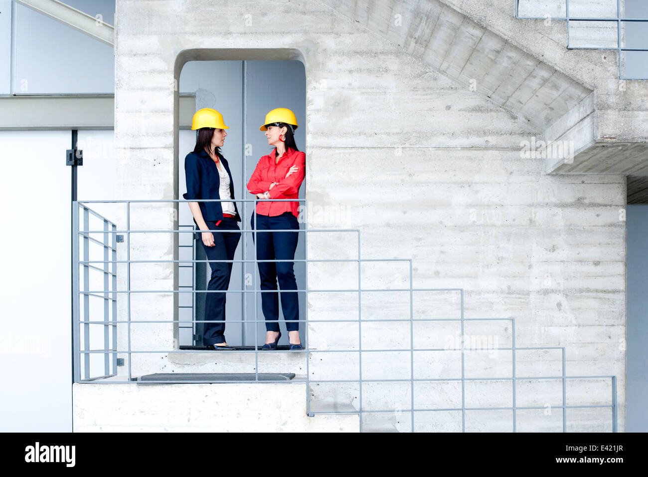 Businesswomen in safety helmet at balcony Stock Photo