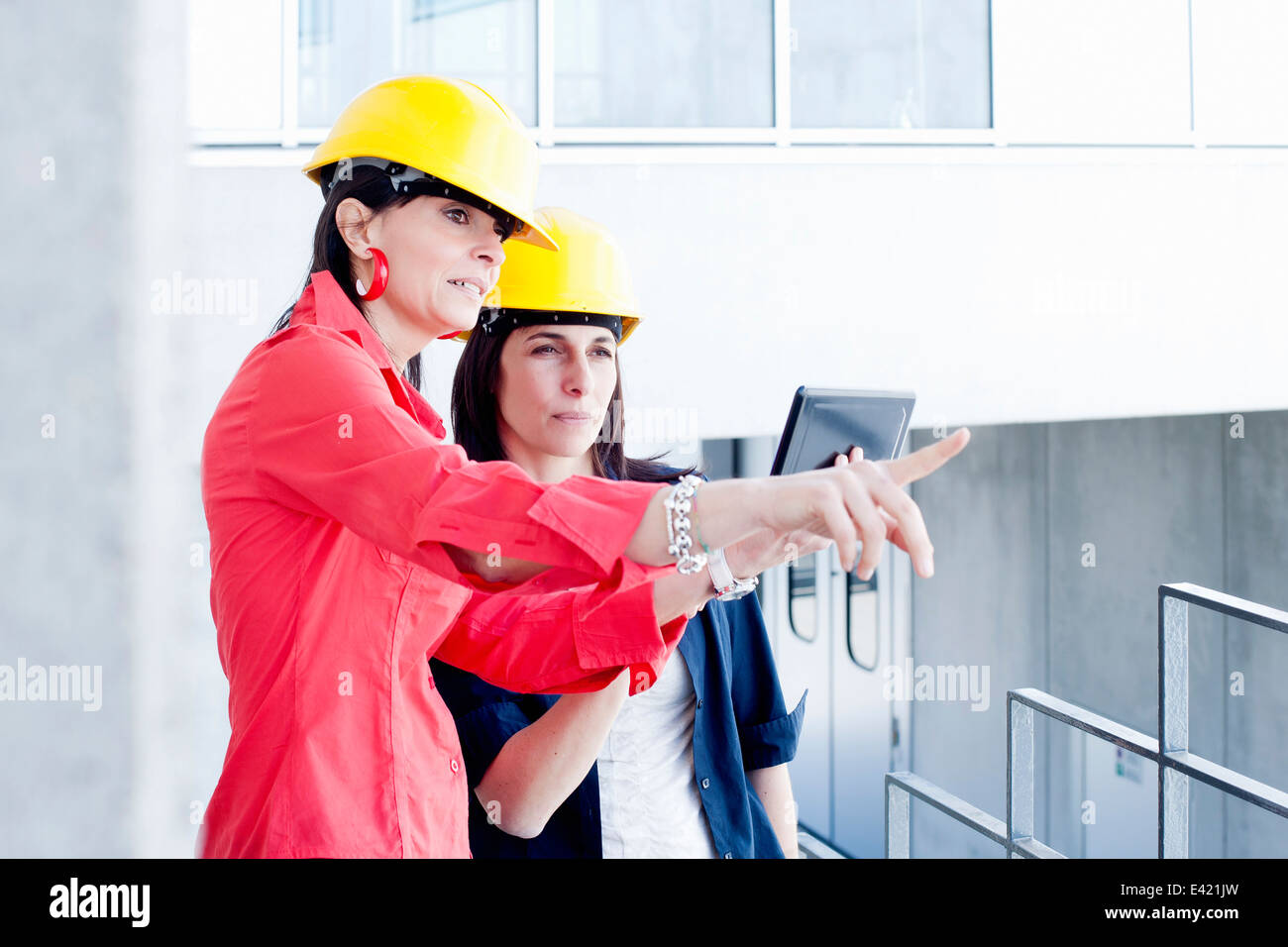 Businesswomen in safety helmet taking photograph - Stock Image