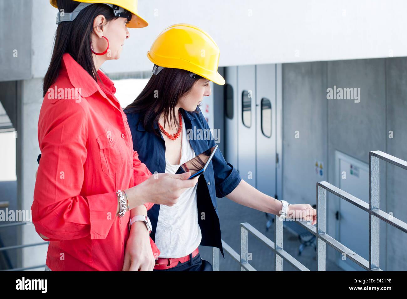 Businesswomen in safety helmet at balcony - Stock Image