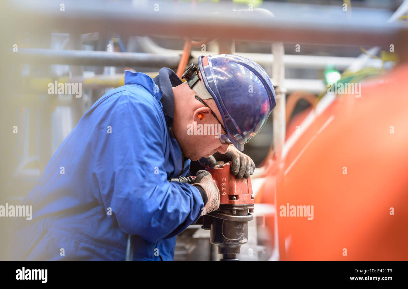 Engineer drilling during power station outage - Stock Image