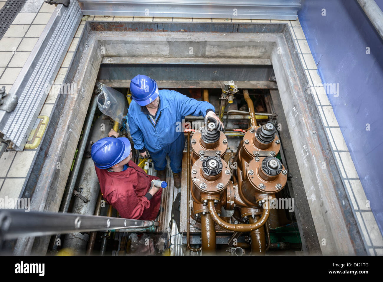 Engineers inspecting electrical unit during power station outage, elevated view - Stock Image