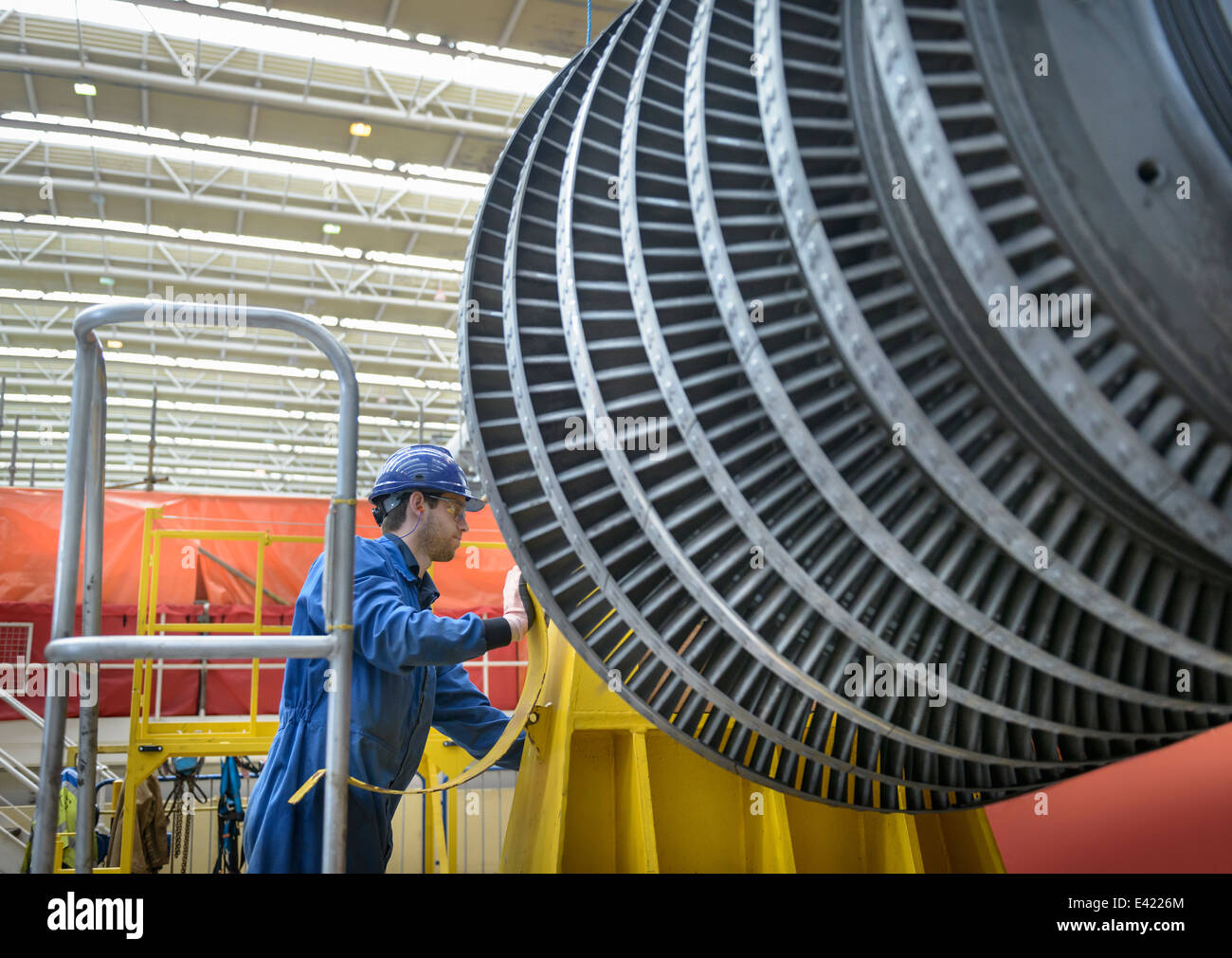 Engineer inspecting turbine during power station outage - Stock Image