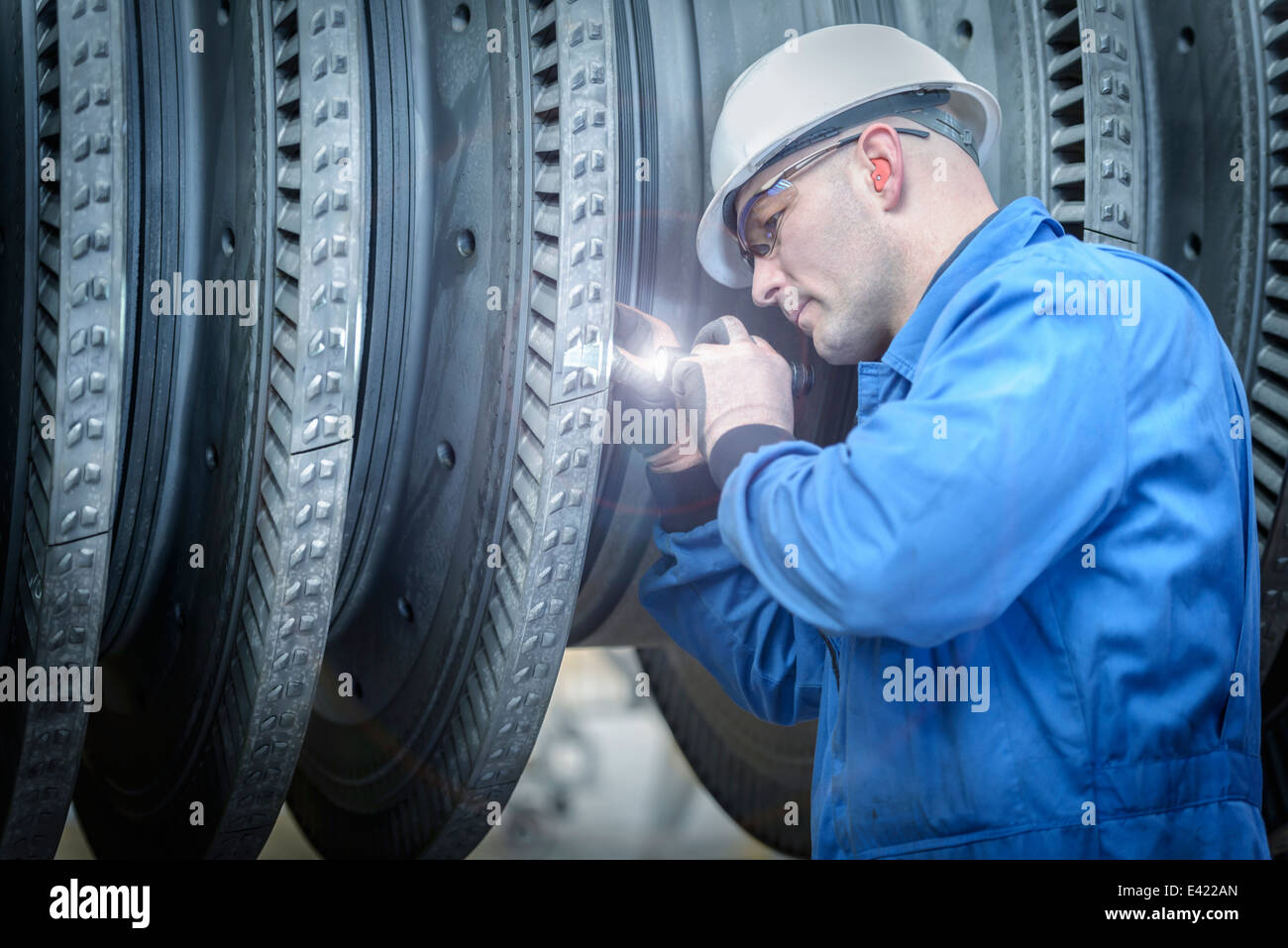 Engineer with torch inspecting turbine during power station outage - Stock Image