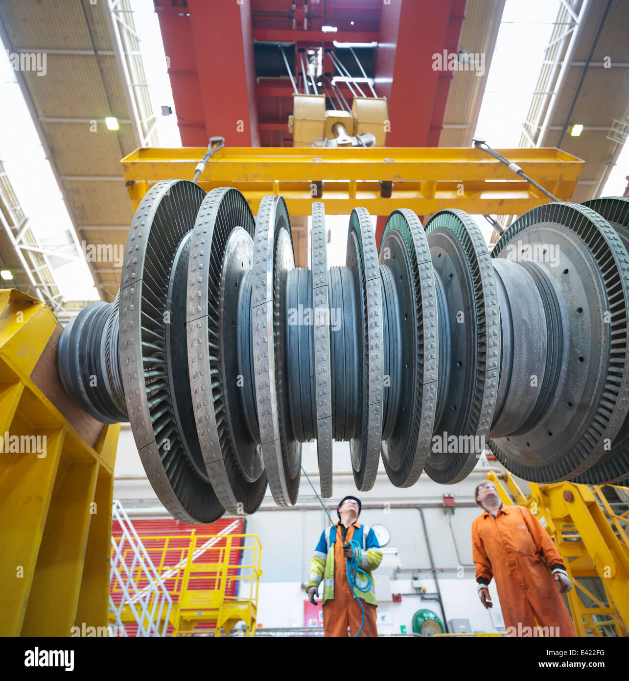 Banksman and crane operator lift turbine during power station outage, low angle view - Stock Image
