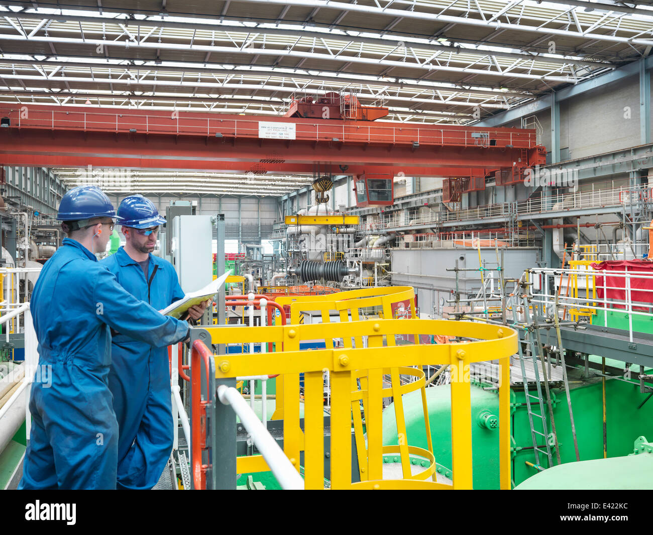 Engineers discussing notes on walkway during power station outage - Stock Image