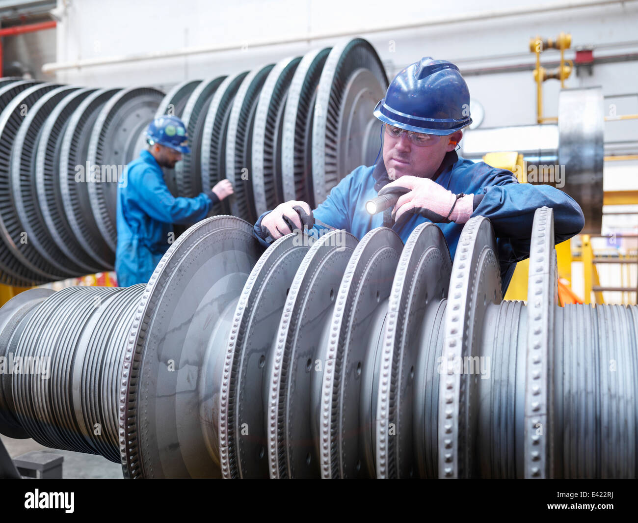 Engineers inspecting turbine during power station outage, portrait - Stock Image