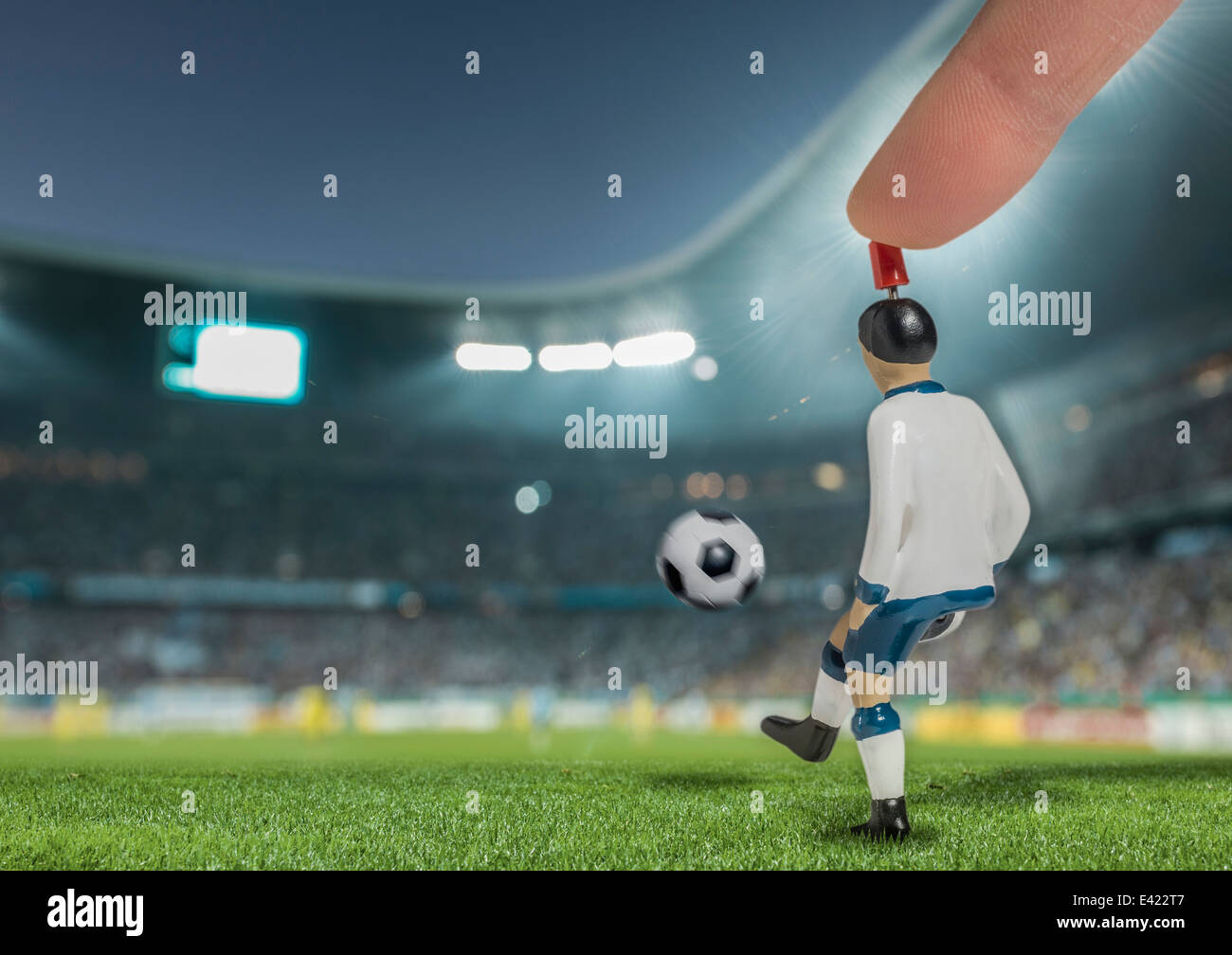 Digitally generated image of soccer player kicking ball in floodlit stadium - Stock Image