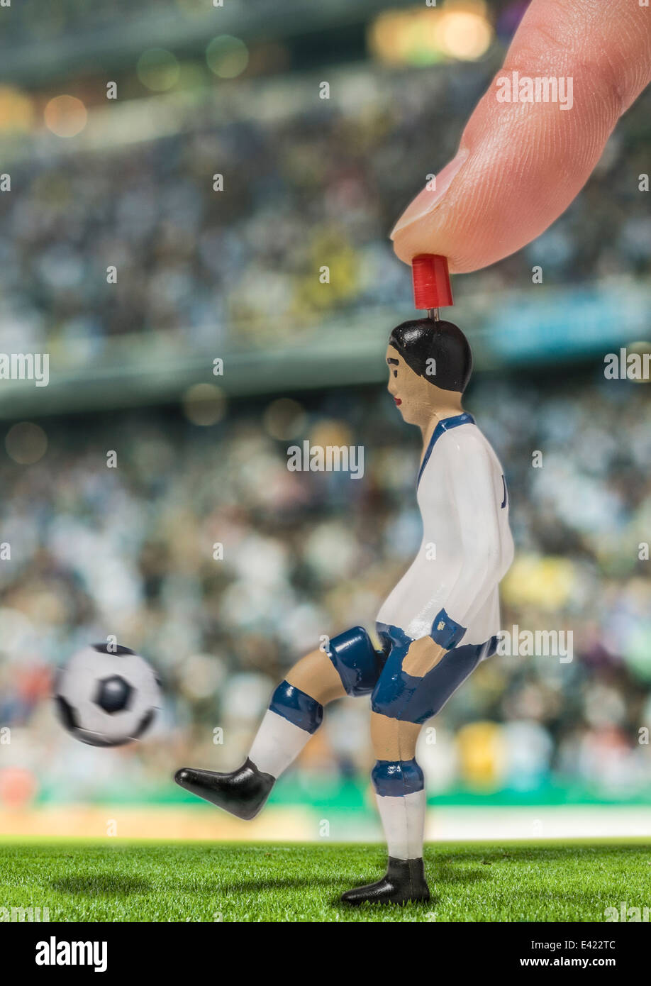 Digitally generated image of soccer player kicking ball in stadium - Stock Image