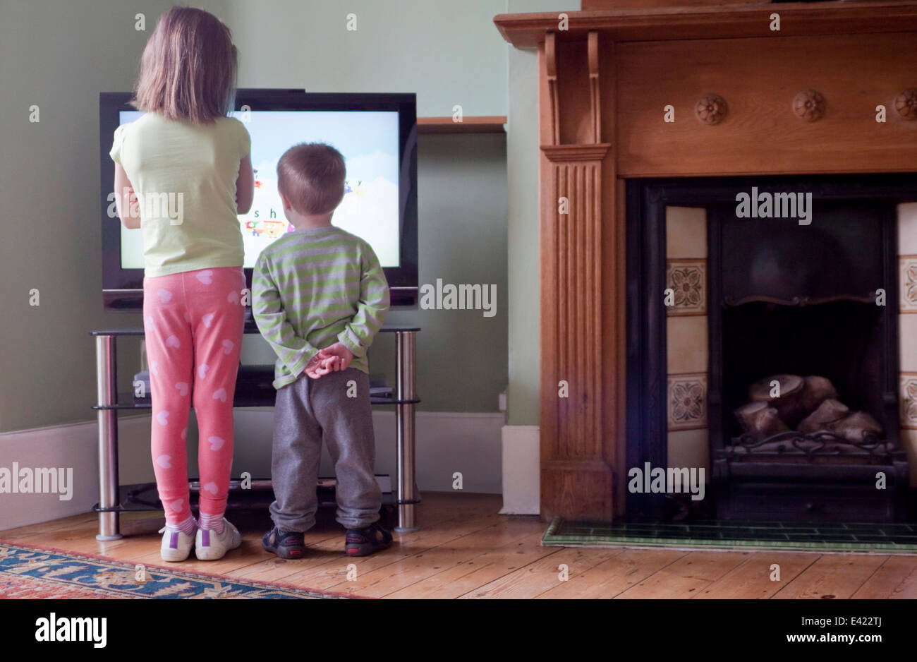 Rear view of sister and brother standing too close to and watching TV - Stock Image