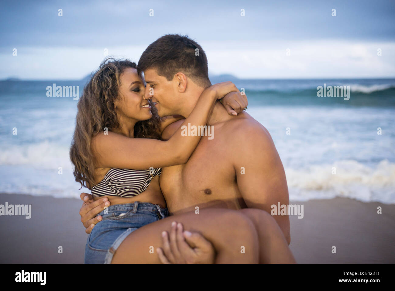 Young man carrying girlfriend in arms on Ipanema Beach, Rio de Janeiro, Brazil - Stock Image
