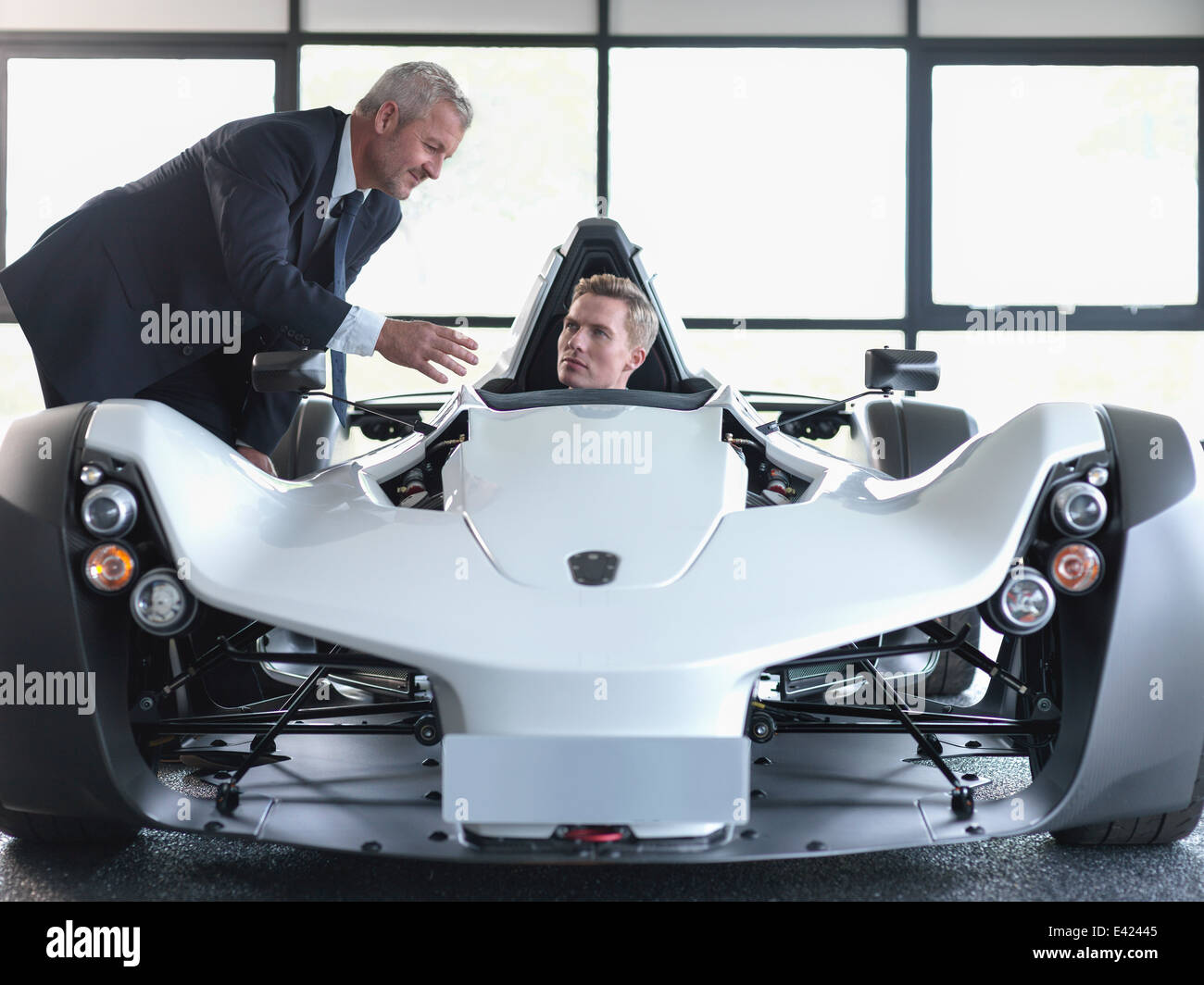Salesman showing customer supercar in show room - Stock Image