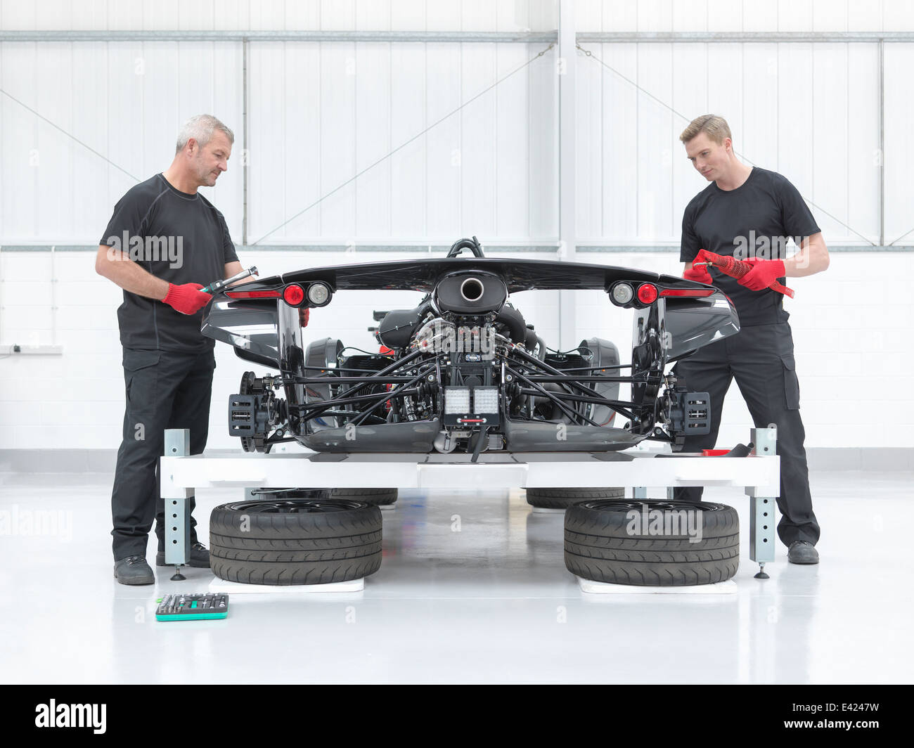 Two engineers assembling supercar in sports car factory - Stock Image