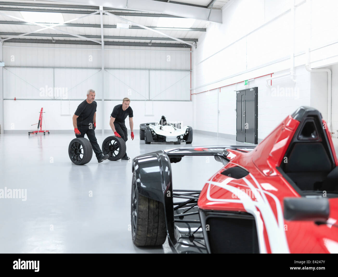 Engineers rolling wheels near supercar in sports car factory - Stock Image