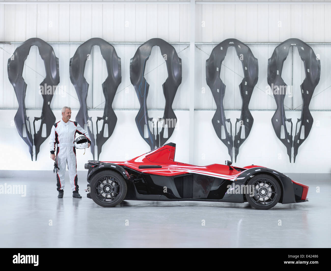 Racing driver with supercar in factory with carbon fibre car body shells hanging on wall - Stock Image