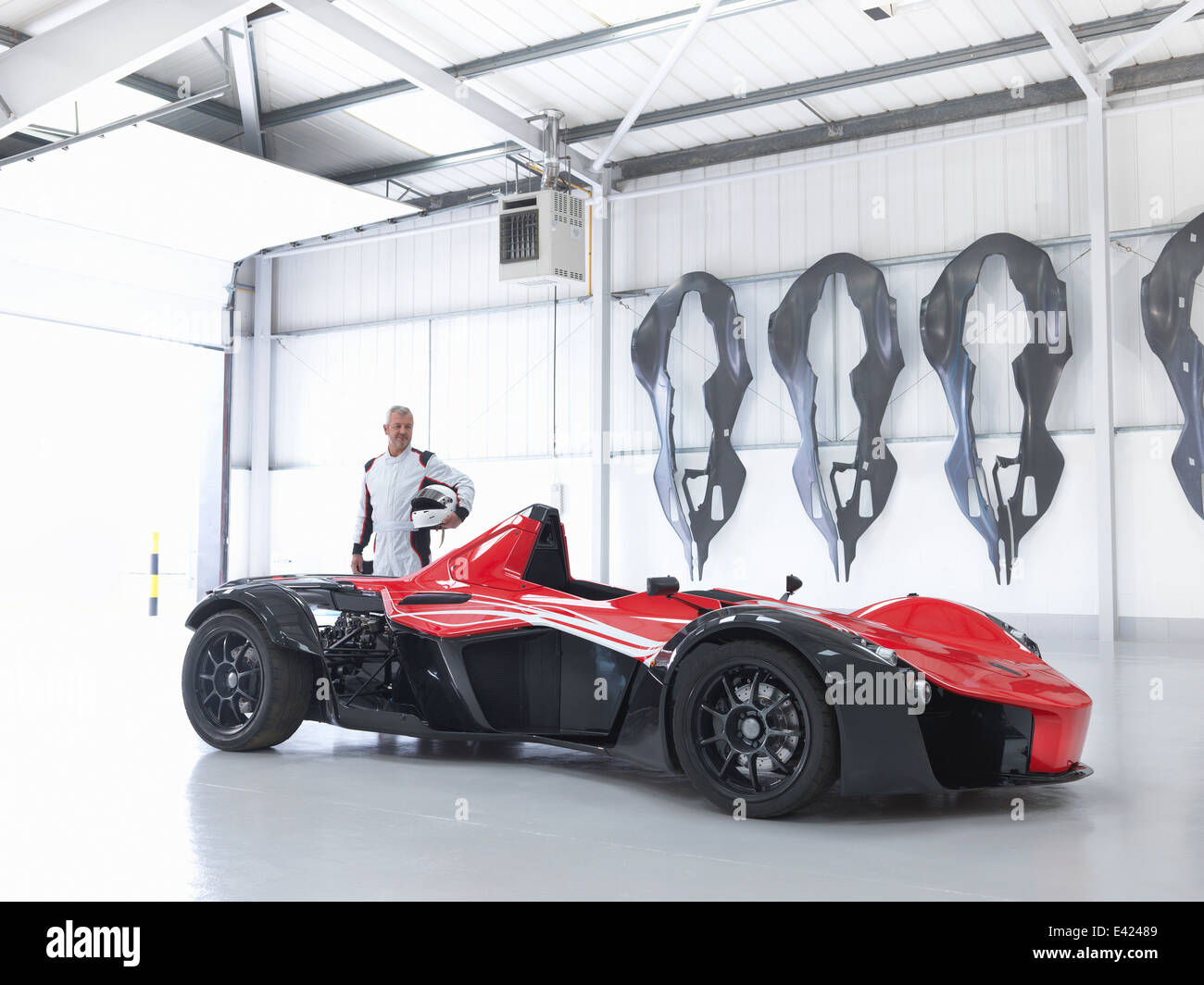 Racing driver with supercar in factory with carbon fibre car body shells on wall - Stock Image