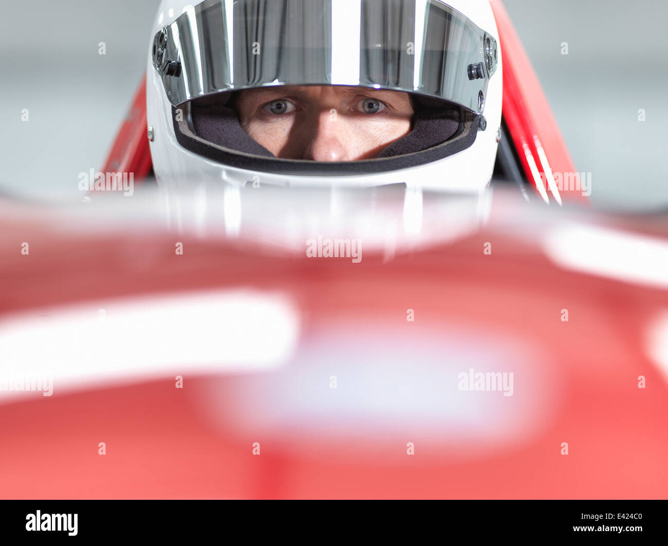 Close up portrait of racing car driver wearing helmet in supercar - Stock Image
