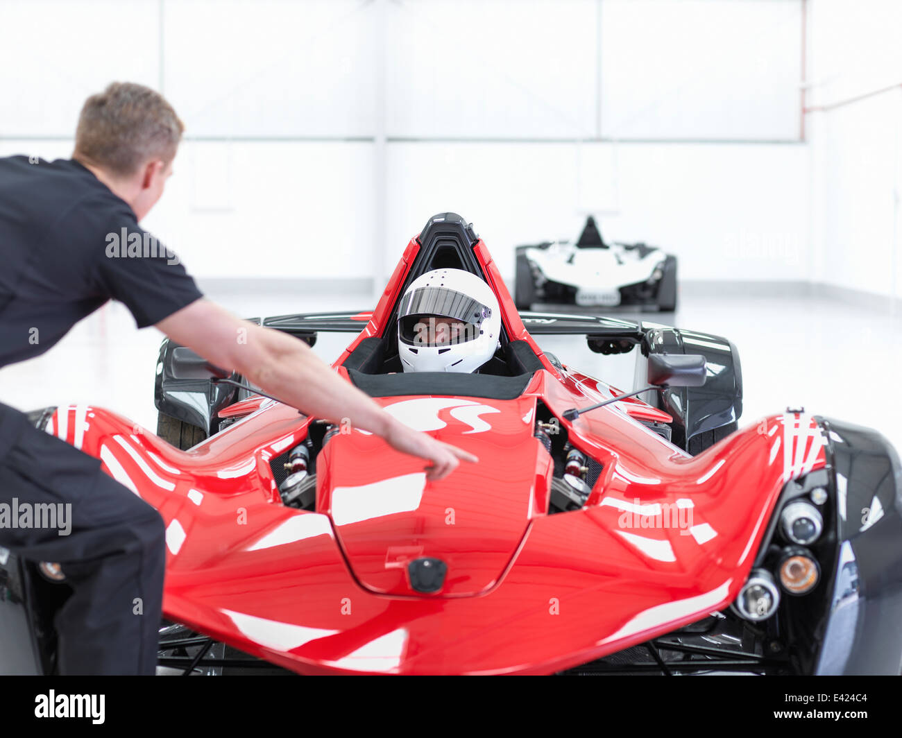 Engineer and racing car driver in supercar in sports car factory - Stock Image
