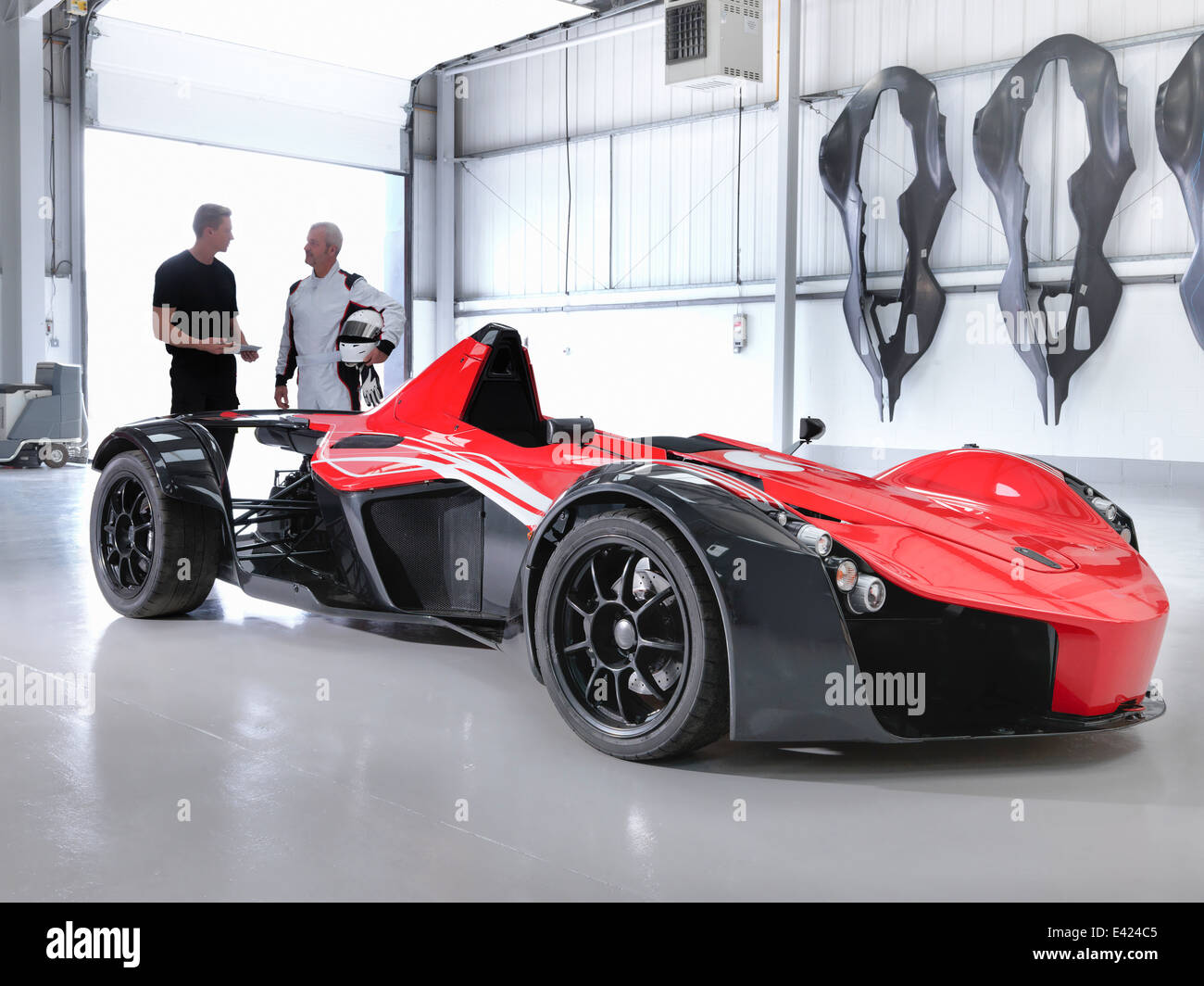 Test driver and engineer with supercar in car factory - Stock Image