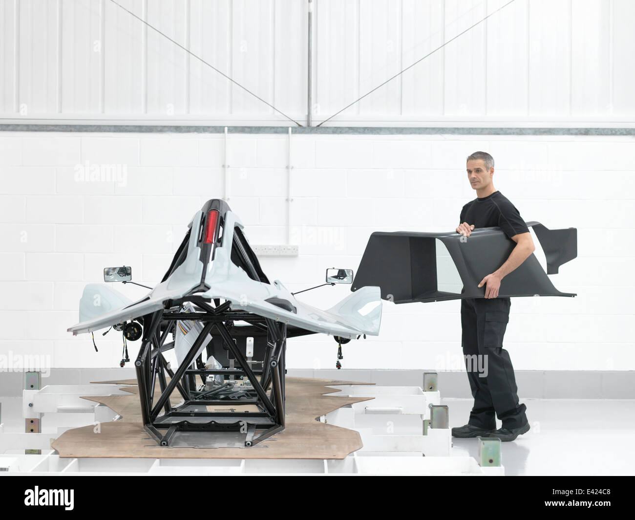 Engineer with part assembled supercar in car factory - Stock Image