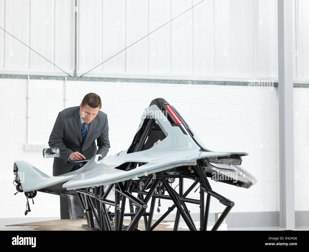 Automotive designer inspecting part-built supercar in car factory - Stock Image
