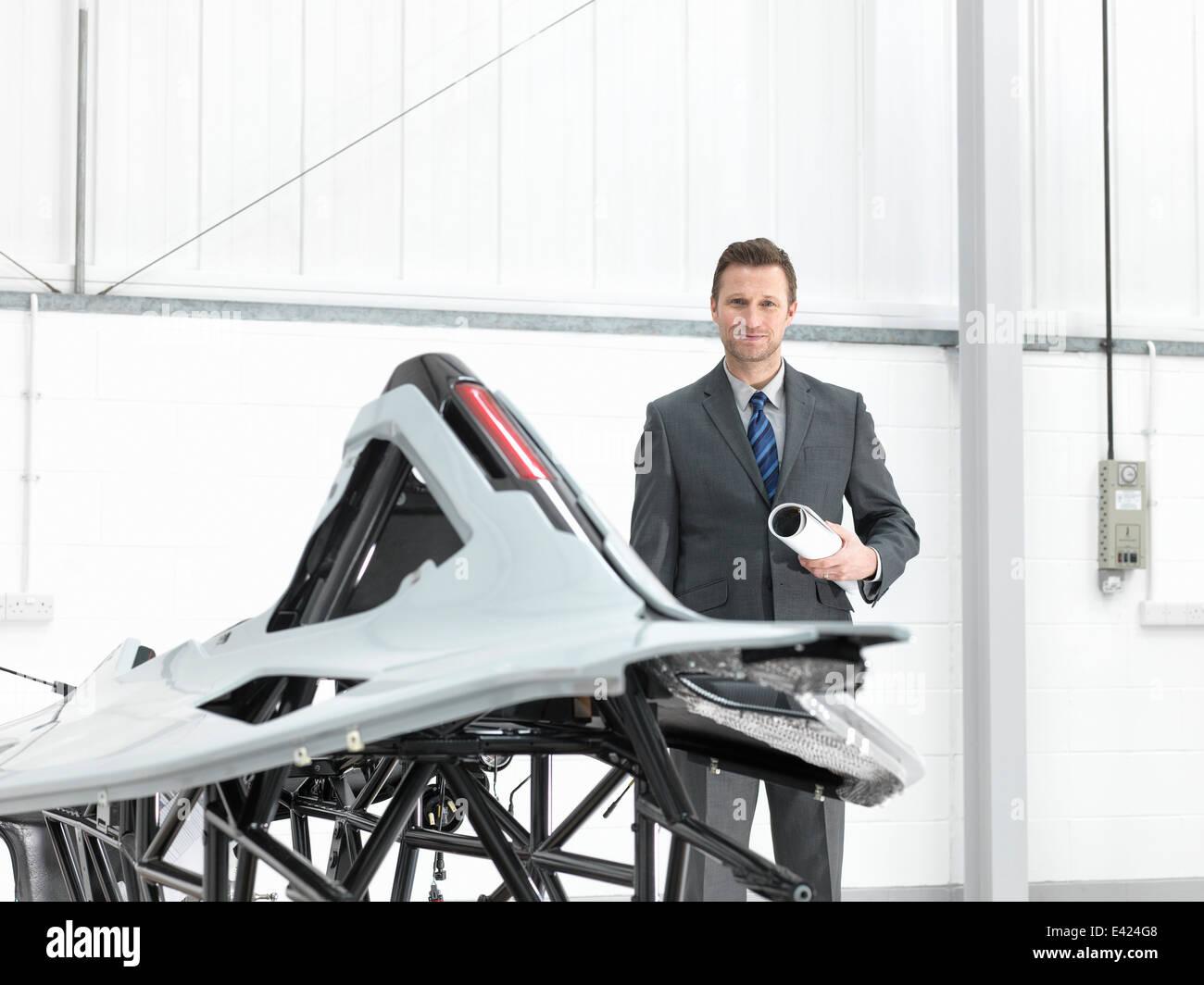 Automotive designer with part-built supercar in car factory, portrait - Stock Image