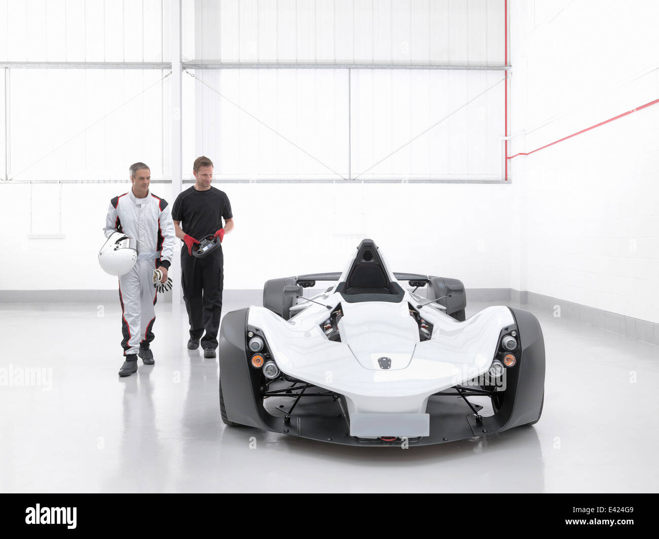 Racing driver with engineer and supercar in car factory - Stock Image