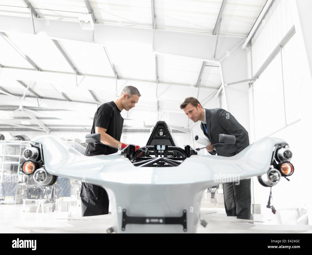 Engineer and automotive designer inspecting part-built supercar in car factory - Stock Image