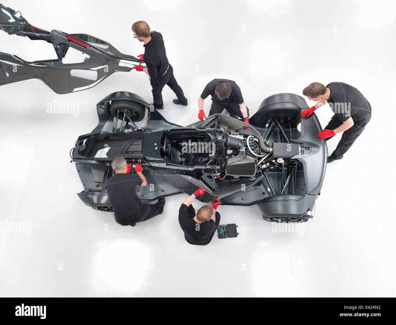 Engineers assemble supercar in sports car factory, overhead view - Stock Image