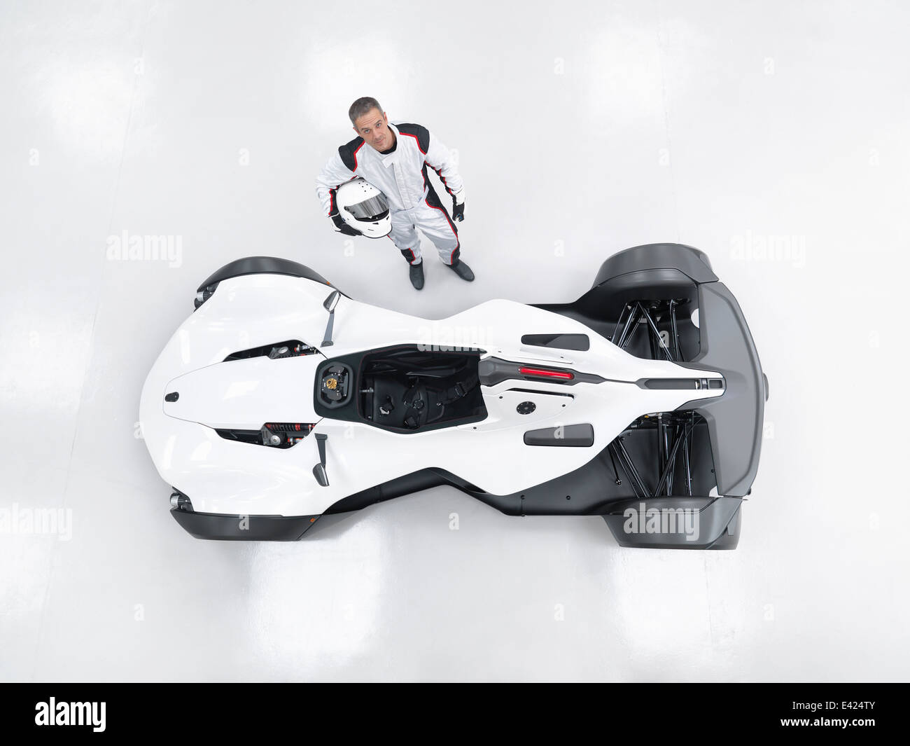 Portrait of racing driver next to supercar, overhead view - Stock Image