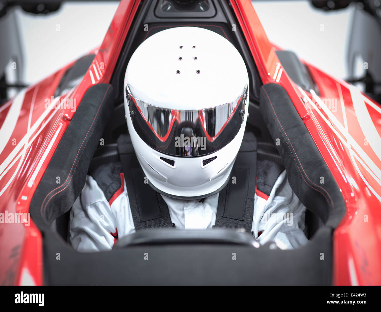 Racing driver wearing crash helmet in supercar - Stock Image