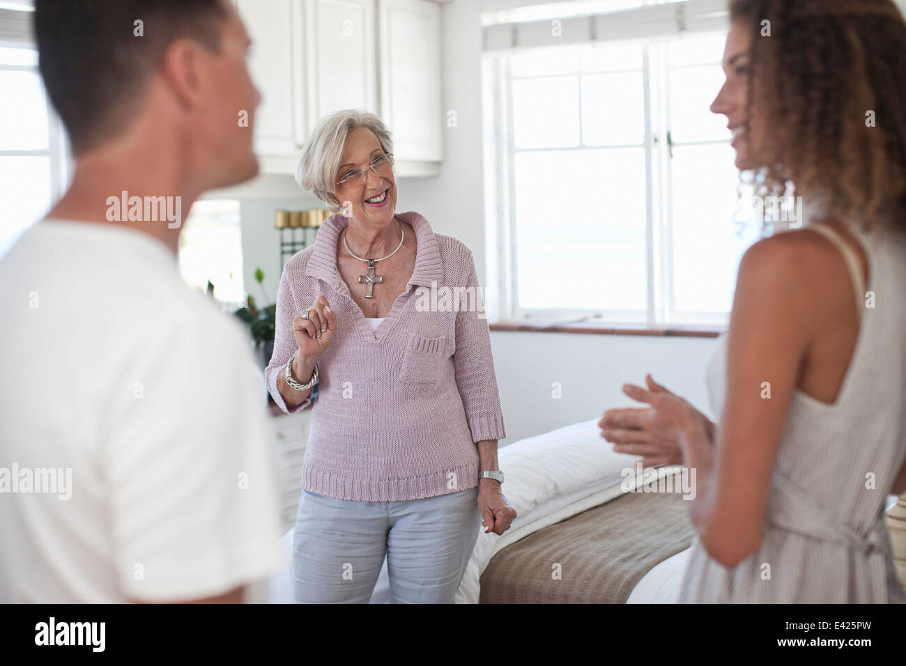 Senior woman guiding couple in holiday apartment - Stock Image
